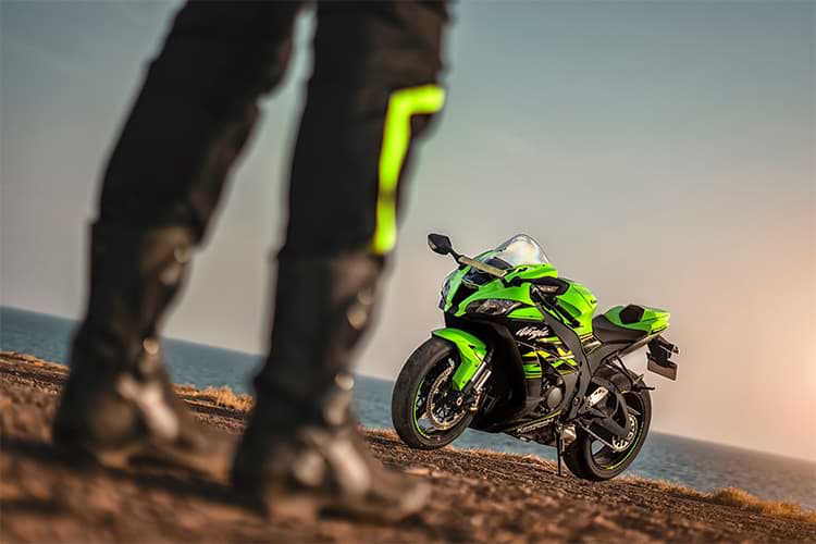Kawasaki ZX10R in the distance in green colour and in focus. The rider's legs near the camera and slightly blurred.